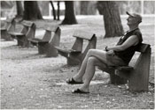 B&W of man sitting on a bench in a park